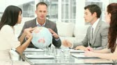 communication : Manager holding a terrestrial globe in a meeting with his team Stock Footage