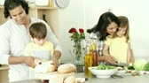 recipe : Footage in high definition of happy family preparing a meal in the kitchen Stock Footage