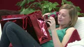 adult : Stock Video Footage of a Woman on Sofa with Christmas Presents Stock Footage