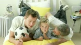 little : Grand farther and grandson watching football while lying on a bed