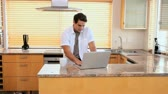 tea : Man using a laptop and drinking a coffee in a kitchen Stock Footage