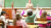 Cute children raising their fingers in the classroom