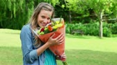 smell : Happy young woman smelling flowers in the countryside Stock Footage