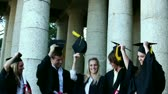 education : Graduates students throwing mortar boards in the air while holding diploma