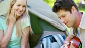 sedução : Man singing a love song with his girlfriend while camping Stock Footage