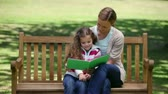 picture : Mother and daughter looking a picture book together sitting on a park bench Stock Footage