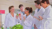 nauka : Students doing plant research with microscope and tablet pc in the laboratory Wideo