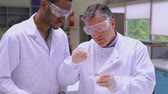 university : Two chemists working with liquid in the laboratory Stock Footage