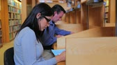 university : Woman and man studying in library Stock Footage