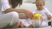 couch : Baby playing with his toys and his mother in slow motion