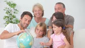 couch : Multi-generation family all looking at globe on the couch  Stock Footage