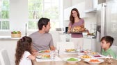 house : Mother taking chicken dish to her family in kitchen