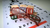reading : Glasses falling onto eye test with wooden blocks spelling out eye test in slow motion