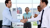 Businessmen shake hands while other business people applauding in a bright office