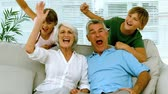 couch : Grandparents and children raising their arms in the living room in slow motion at 250 frames per second Stock Footage