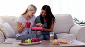 couch : Suprised woman being offered a box of chocolates while she is sitting on the couch Stock Footage