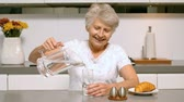 meal : Happy woman pouring a glass of water for breakfast in the kitchen in slow motion