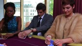 play : People being dealt poker cards with two people folding and one placing bet in the casino