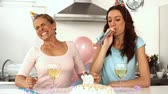 household : Woman blowing candle while celebrating her birthday with a friend wearing party hat and party horns in slow motion  Stock Footage