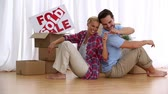 household : Couple sitting back to back laughing and happy to be in new home Stock Footage