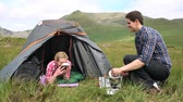 conversation : Man handing his girlfriend a bowl of soup on a camping trip in the countryside Stock Footage