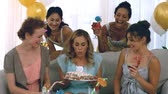 making a wish : Woman blowing out birthday candles with her friends