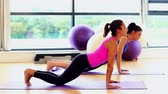 calm : Two slender attractive women practising yoga in fitness hall Stock Footage