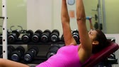 dispositivo : Fit attractive woman lying on exercising device while lifting dumbbells