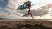 lifestyle : Woman bouncing at the beach holding a scarf in slow motion