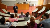 conferencista : Lecturer speaking to his class in the lecture hall at the university