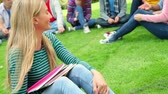 campus : Blonde student smiling at camera with friends behind her on grass at the university