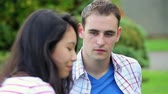 campus : Students having a conversation on the grass on college campus Stock Footage