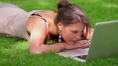 university : Smiling student lying on grass looking at laptop on college campus
