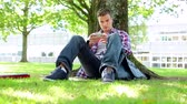 calm : Young student sitting on the grass texting on college campus