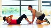 lifestyle : Handsome coach supporting young woman doing situps in fitness hall