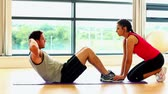 lifestyle : Cute fit man doing situps in fitness hall being supported by female coach
