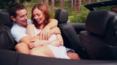 calm : Attractive couple embracing and chatting in a convertible car Stock Footage