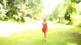 fashion : Beautiful teen walking towards camera on a sunny day in a green park Stock Footage