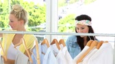 lifestyle : Friends looking through clothing rail together at fashion boutique