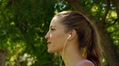 lifestyle : Runner drinking water and listening to music in the park on a sunny day