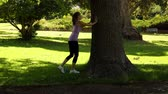 lifestyle : Runner stretching her legs leaning against tree on a sunny day Stock Footage