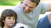 lifestyle : Father sitting with little son holding football in the park on a sunny day