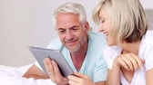 calm : Happy couple lying on bed using tablet together at home in bedroom
