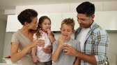 dunking : Children having milk and cookies with their parents at home in the kitchen Stock Footage