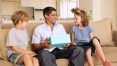 opening : Cute children giving their father presents on the couch at home in living room