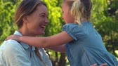 pasture : Young mother giving her daughter a hug in the park in slow motion