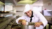 preparations : Handsome chef stirring a large pot in commercial kitchen Stock Footage