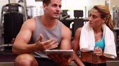 fitness : Fit woman and trainer talking about her progress at the gym