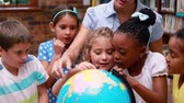 planety : Pupils looking at the globe in library with their teacher in elementary school Wideo