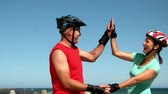 slowmotion : Senior couple roller blading along the pier and high fiving in slow motion